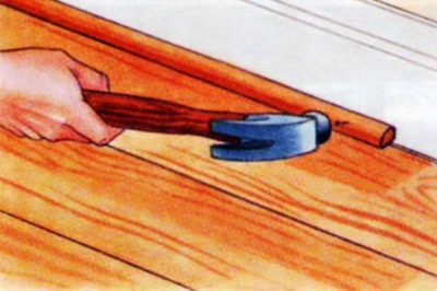 Прибивают деревянный плинтус гвоздями