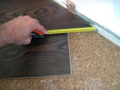 Прежде, чем обрезать край ламинатной доски, необходимо точно измерить расстояние от ламинатного ряда до распорных колышек