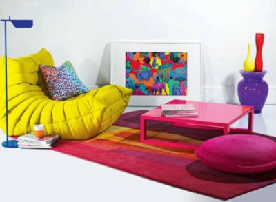 Цвет фуксии на ковре повторяется в обивке пуфика и расцветке журнального столика