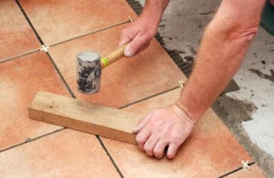 Для выравнивания плитки по ней стучат резиновым молотком