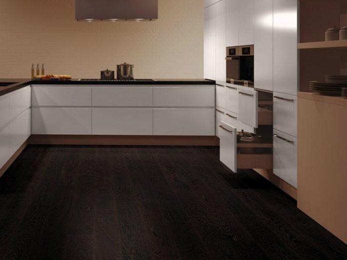Интерьер кухни с белым гарнитуром и темным полом