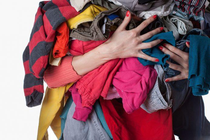 Девушка с горой одежды в руках
