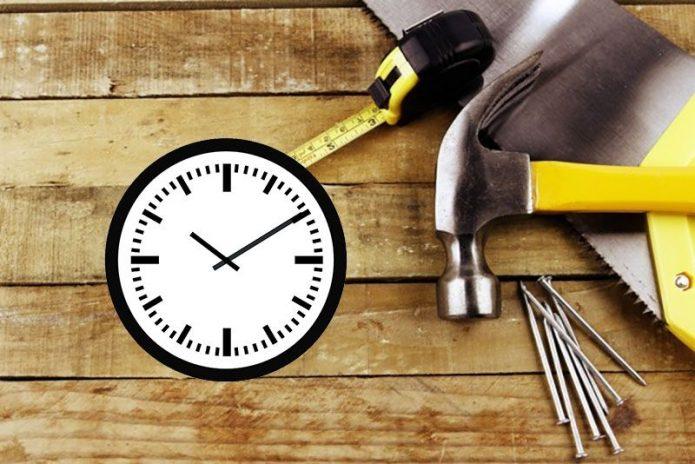 Строительные инструменты возле циферблата часов