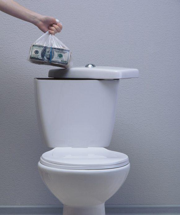 Пакет с деньгами в руке возле бачка унитаза
