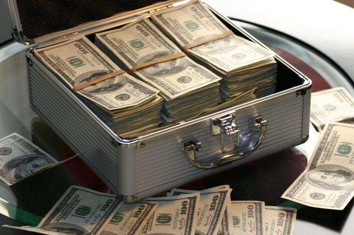 Доллары в чемодане и возле него