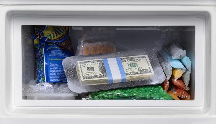 Пачка долларов в морозильной камере рядом с продуктами