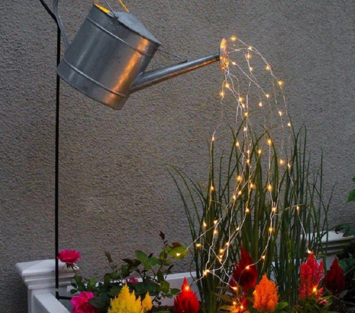 Колоритный светильник над клумбой из дачной лейки