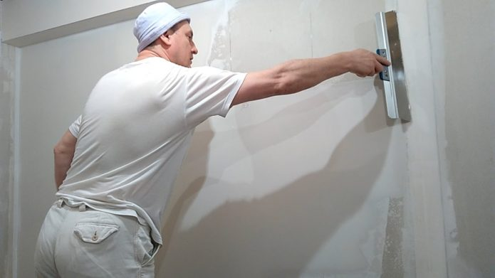 Мастер шпатлюет стену