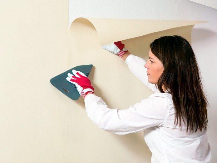 Девушка клеит обои на стену