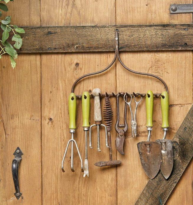 Оригинальная вешалка для садовых инструментов на двери сарая