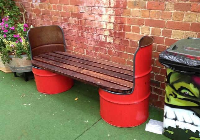 Садовая скамейка из досок и металлических бочек