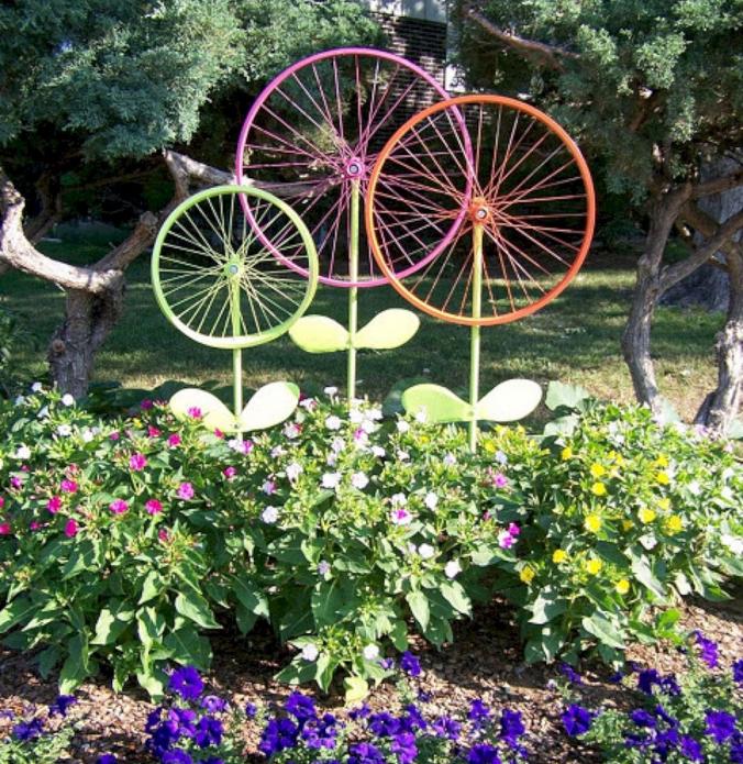Колоритный декор из колёс на садовой клумбе