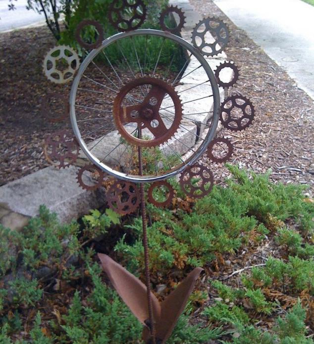 Декор из колеса и лопат на дачной клумбе