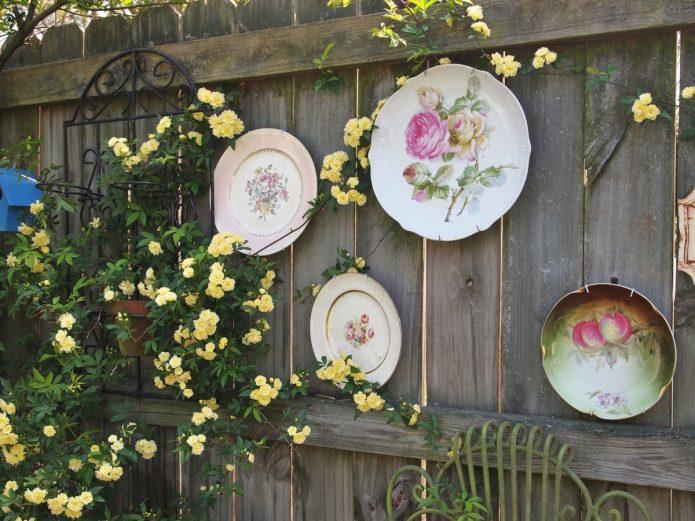 Нарядный декор из тарелок на дачном заборе