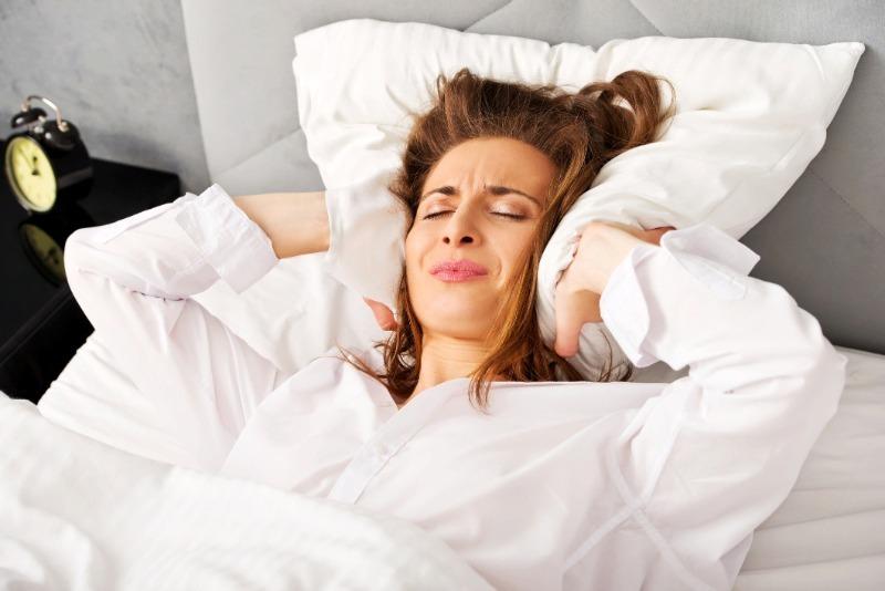 Девушка в кровати закрыла подушкой уши